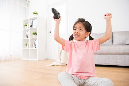 Foto de attractive little girl kid winning online video game raised her hands to celebrate victory and holding joystick controller sitting on wooden floor at home. - Imagen libre de derechos