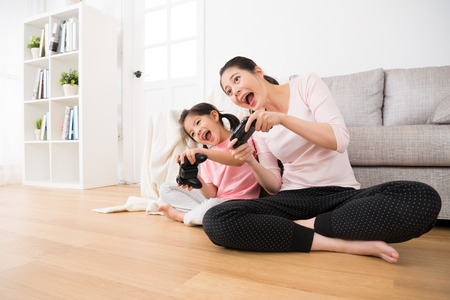 Foto de beautiful little girl children and pretty housewife mom leisurely relax playing tv video game and holding controller with game to move body sitting together in family lounge wood floor. - Imagen libre de derechos