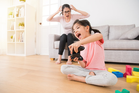Photo pour happy young little girl children holding controller playing video games in living room wooden floor with many colorful toy while her mad mother very angry showing crazy emotion on sofa. - image libre de droit