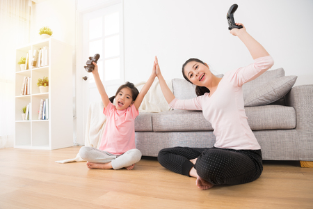 Foto de happiness family happy mother and excited daughter sitting in living room wood floor clapping together and hold controller raised hands for celebrate video games winning. - Imagen libre de derechos