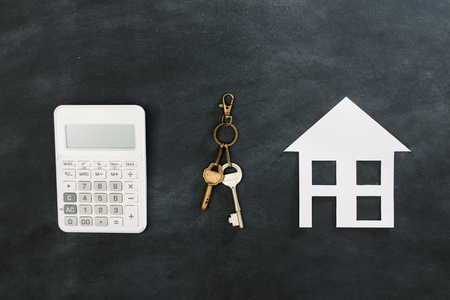 Foto de high angle view photo of calculator tool with key showing buying new house concept isolated on black chalkboard background. - Imagen libre de derechos