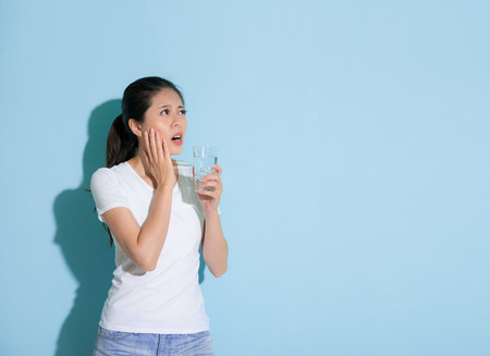 Photo pour pretty elegant woman holding ice water hand on sensitive teeth part and looking at empty area thinking about solution standing in blue wall background. - image libre de droit