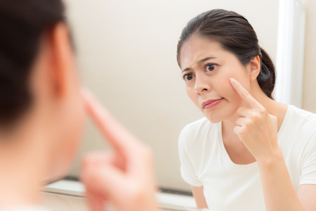 Foto de young cute female student annoying face having acne problem during puberty standing in bathroom look at mirror reflection image. - Imagen libre de derechos