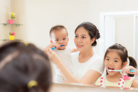 Photo pour happiness family daily life photo of young mother with kid looking at mirror using toothbrush cleaning teeth in bathroom together every morning and night. - image libre de droit