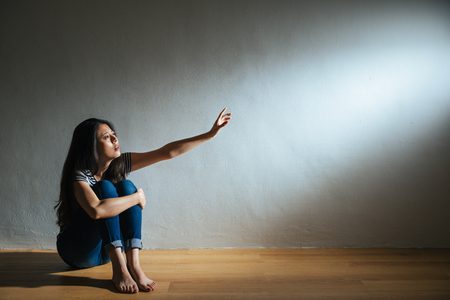 Foto de battered abused woman concept of lonely victim sitting on white background wood floor in dark and sadness looking at light need help. - Imagen libre de derechos