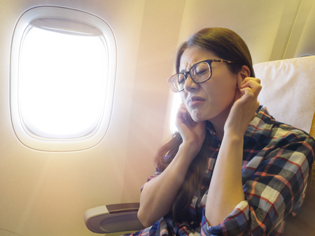 Foto de lovely sweet female traveler feeling ear painful when airplane take off getting tinnitus. - Imagen libre de derechos