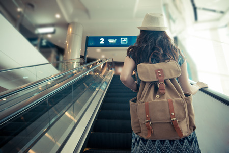 Photo for vintage retro film color photo. back view of female traveler carrying backpack and standing on electric escalator going to gate when she arrived airport. - Royalty Free Image