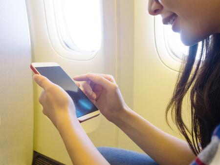 Foto de closeup photo of smiling beautiful traveler sitting in airplane window seat and using mobile smartphone watching travel information. - Imagen libre de derechos