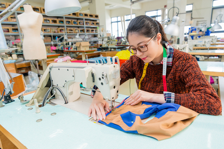 Foto de pretty professional female sewing worker using tailor machine making designer new product in fashion studio. - Imagen libre de derechos