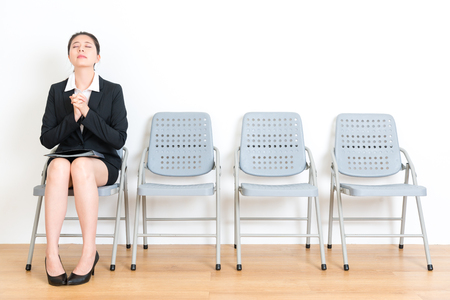 Photo for lovely sweet female fresh graduate wearing suit waiting new work interview and sitting on wood floor chair making pray gesture hopping successful in white wall room. - Royalty Free Image
