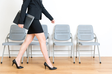 Foto de beautiful young suit female model holding company data file finished interview meeting walking on wood floor in white wall background with chairs. - Imagen libre de derechos