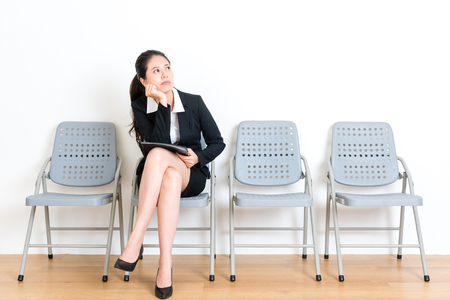 Photo for beauty lovely business woman prepare company data file sitting on wood floor chair in white wall room waiting for interview meeting feeling bored looking at empty area fantasy. - Royalty Free Image