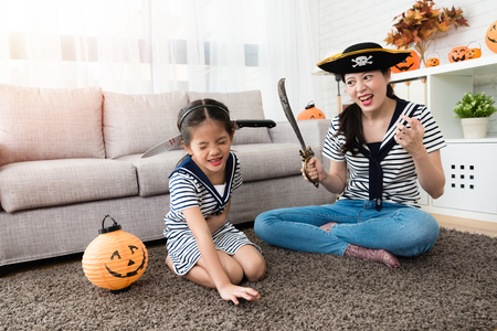 Foto de horror pirate mother play the killing game with her cute girl and put the knife on her head for Halloween holiday in the living room - Imagen libre de derechos