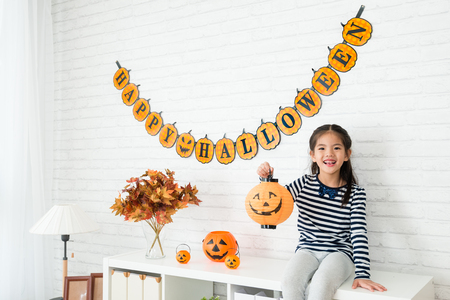 Foto de happy kids holding a pumpkin lantern and sitting on the cabinet of the living room after help her family to decorating - Imagen libre de derechos