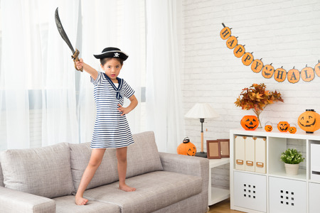 Foto de little pirate girl holding knife showing her determination to fight for Halloween game at the party - Imagen libre de derechos
