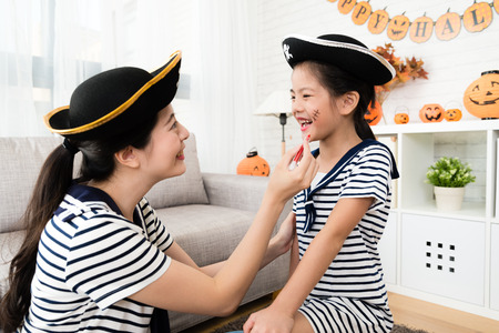 Photo for pirate girl and mother have fun with Halloween makeup drawing scars on the face at home - Royalty Free Image