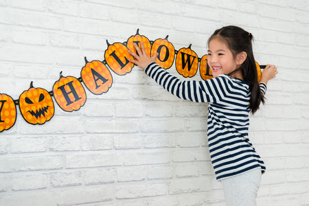 Foto de sweet kids help her family to hang up the decoration to celebrate the Halloween holidays at home. - Imagen libre de derechos