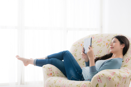 Foto de happy smiling woman lying down on sofa chair using mobile digital tablet and watching online video movie relaxing during sunny holiday. - Imagen libre de derechos