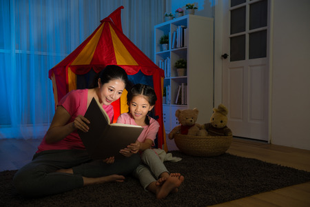 Photo pour slim smiling lady and happy leisurely child sitting in front of toy tent reading story comic book together on bed room at night. - image libre de droit