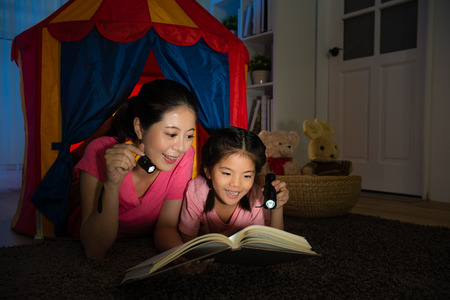 Foto de elegant smiling mom with smiling cute children lying in toy tent together and holding torch flashlight reading bedtime story book at night in bed room. - Imagen libre de derechos