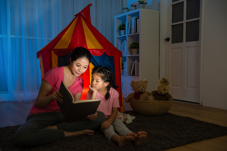 Photo pour attractive elegant woman sitting on living room floor with beauty calm kid and holding story book together reading at night in holiday vacation. - image libre de droit