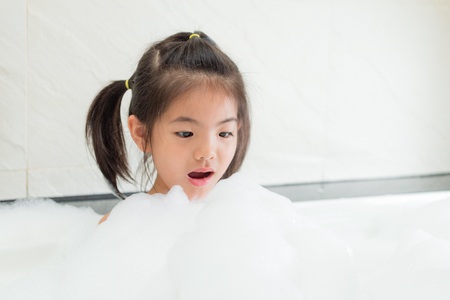Foto de beautiful attractive little girl feeling surprised looking at white bubble when she washing body in bathroom and relaxing on bathtub. - Imagen libre de derechos