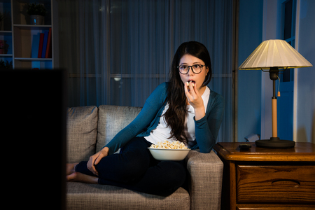 Photo pour elegant beauty woman looking at television enjoying new movie and eating tasty popcorn snack sitting on living room sofa at holiday night. - image libre de droit