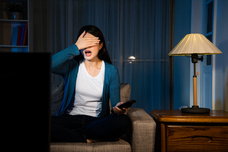 Photo for young lovely girl watching movie looking at terrible plot raised hand covering eyes and showing fear emotional sitting on living room sofa at night. - Royalty Free Image