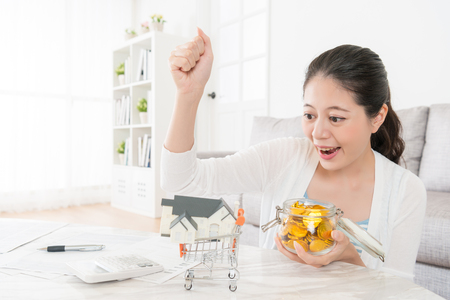 Photo for beautiful cheerful girl making successful gesture looking at house model celebrating her personal deposit can buying new apartment. - Royalty Free Image