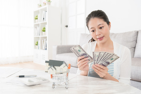 Foto de beauty attractive woman counting cash banknote money in living room and planning using deposit buying new house for family. - Imagen libre de derechos