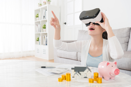 Foto de happy elegant mother planning using family deposit buying new house and watching 3D building video information to choosing suitable apartment through virtual reality device. - Imagen libre de derechos