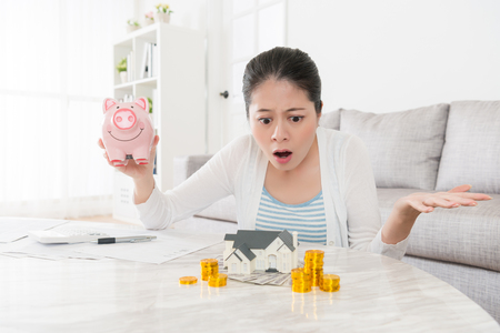 Photo pour young pretty housewife holding piggy bank sitting in living room and looking at house model feeling dumbfounded because her deposit not enough buying new apartment. - image libre de droit