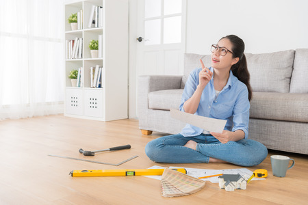 Foto de happy pretty housewife holding new house interior sketch paper daydreaming and thinking good idea making pointing gesture sitting in living room wooden floor. - Imagen libre de derechos