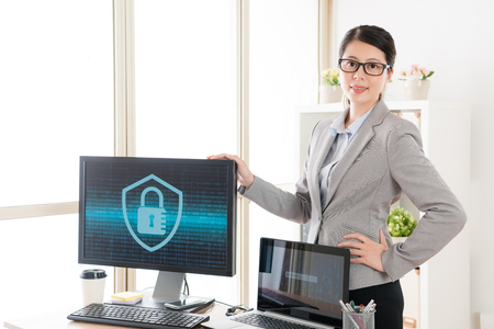 Foto de pretty beauty cyber security business woman face to camera in office with company computer. - Imagen libre de derechos