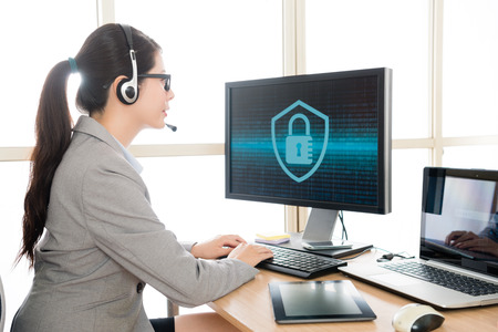 Photo pour professional pretty female office worker wearing headset talking with customer and typing data into online system to solve cyber security problem. - image libre de droit