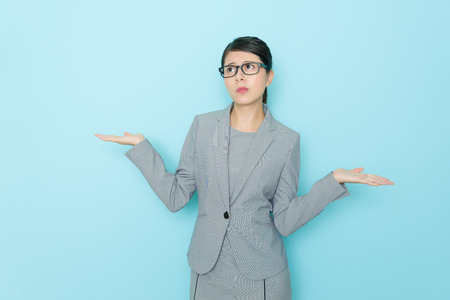 Foto de pretty elegant female lawyer making choosing posing feeling confused and standing in blue wall office thinking about how to decision. - Imagen libre de derechos