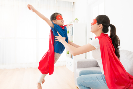 Foto de pretty young mother holding cute little girl making fly posing and playing as superhero at home. - Imagen libre de derechos