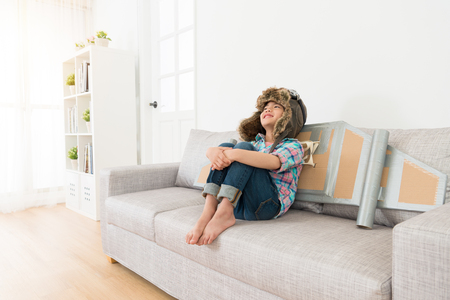 Photo pour happy cheerful little kid girl wearing astronaut costume sitting on living room sofa daydreaming. - image libre de droit