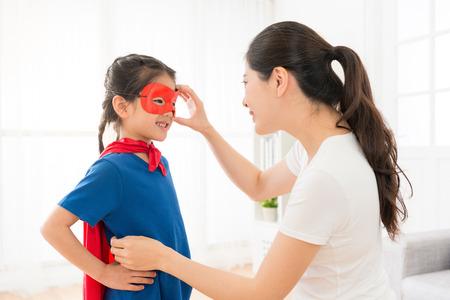 Foto de beautiful sweet girl kid wearing red cloak play as superhero and elegant young mother helping her adjusting mask in living room at home. - Imagen libre de derechos