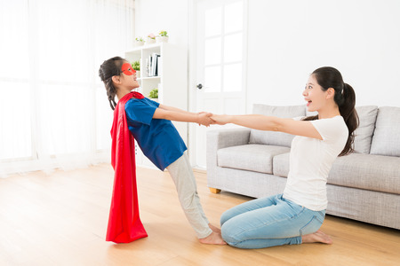 Photo pour happy pretty children girl wearing superhero clothing with beautiful cheerful mother hand in hand at home enjoying funny time. - image libre de droit