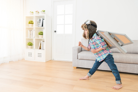 Photo pour pretty young little girl wearing astronaut costume standing on living room wooden floor and making running posing ready to fly at home. - image libre de droit