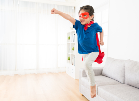 Photo for attractive sweet little girl jumping from sofa couch to fly when she play as superhero with cloak and mask at home in living room. - Royalty Free Image