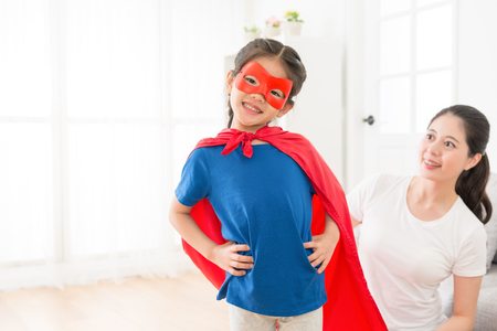 Foto de youth beautiful little kid girl face to camera wearing red cloak with mask play as superhero and beauty smiling mother looking at her. - Imagen libre de derechos