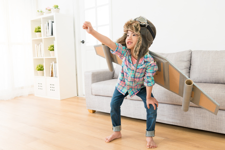 Photo pour smiling sweet female children wearing astronaut costume making ready to fly gesture standing on living room wooden floor at home. - image libre de droit