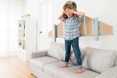 Photo pour happy sweet little girl children wearing astronaut costume standing on living room sofa couch and using hands cover her eyes playing hide and seek. - image libre de droit