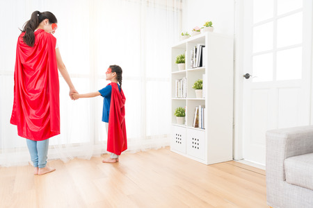 Photo pour back view photo of happy mother and little daughter wearing red cloak with mask looking each other playing as superhero standing in front of living room window. - image libre de droit