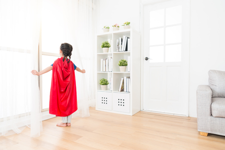Photo for back view photo of youth lovely little girl children playing as superhero and standing on living room wooden floor opening curtain looking at window. - Royalty Free Image