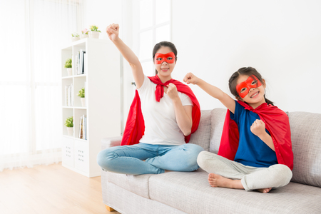 Foto de smiling pretty mother with lovely young little daughter sitting on sofa couch face to camera and play as superhero making same posing ready to fly. - Imagen libre de derechos