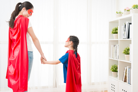 Photo for closeup photo of smiling woman with lovely little girl looking each other and playing as superhero together at home in summer vacation holiday. - Royalty Free Image