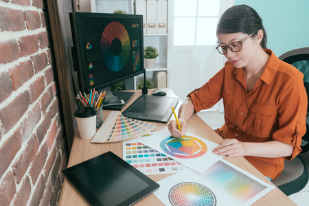 Photo for professional young female graphic designer choosing design color in office. - Royalty Free Image